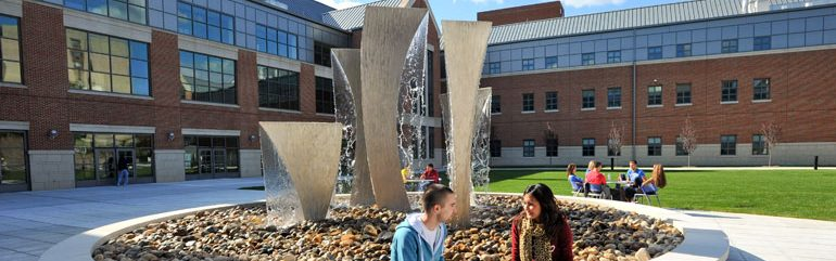 Waterbury students relaxing outside the fountain in the campus courtyard.